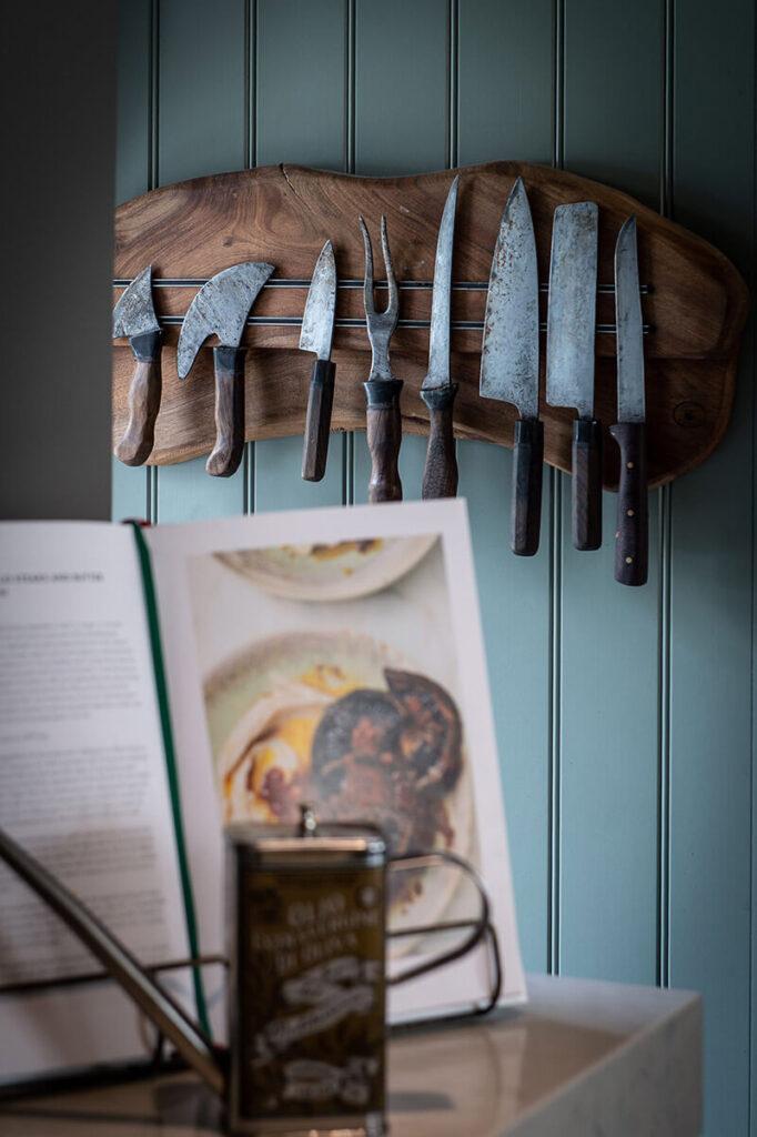 A set of antique knives hanging on the side of larder cabinet