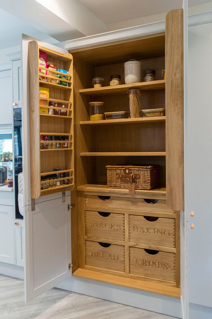 The bespoke pantry which when opened, reveals some beautiful natural wooden shelving and storage units with wording chosen by the customer