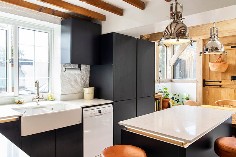 The white worktops work well with the stone walls as well as the rustic wooden beams and door