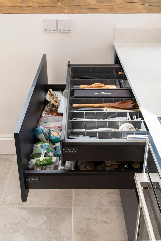 Pullout storage, floor-to-ceiling larder cupboards and the rustic wooden shelving all offer plenty of practical storage.