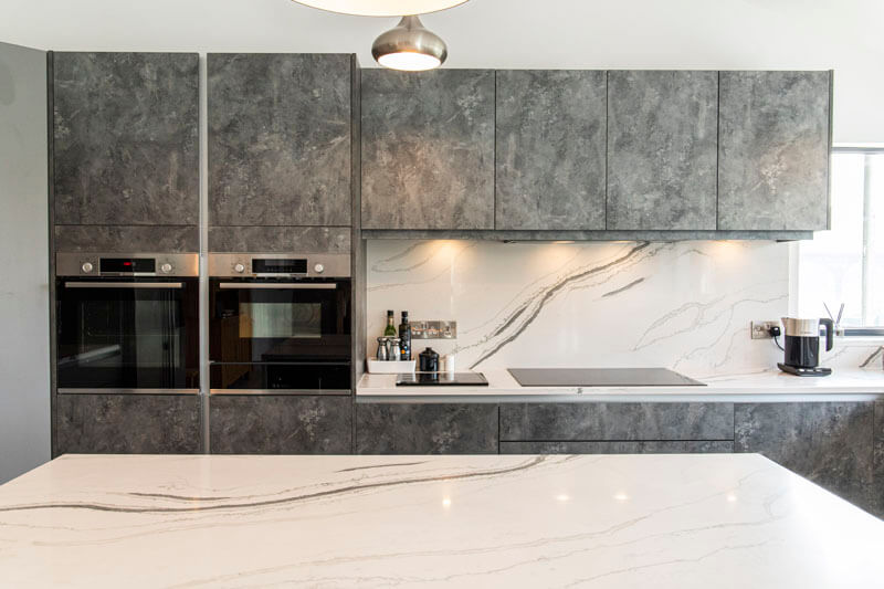 Our Cary handleless kitchen door which is finished in both Dust Grey and a unique Anthracite metal rock