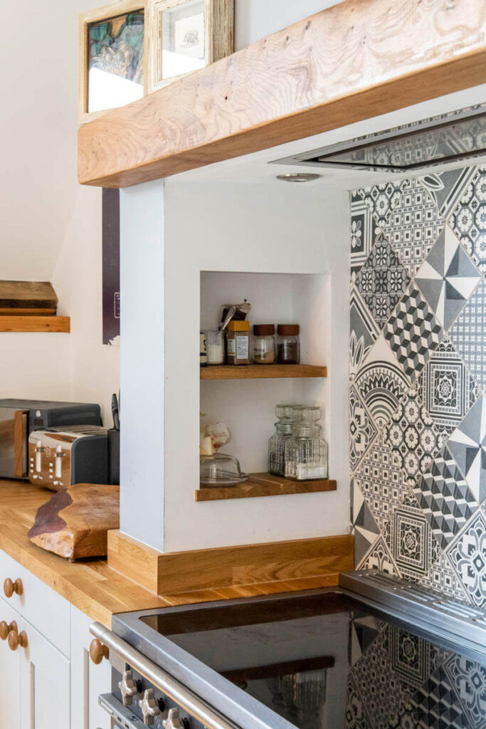 Oak worktops and bespoke shelving above the range cooker blend seamlessly with the exposed wooden beams